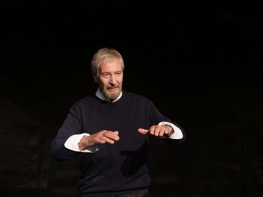 Wolfgang Keuter im schwarzen Bühnenraum. Er zeigt mit einer Handgebärde eine Methoder der Leib-Wahrnehmung